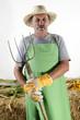 Biobauer mit einer Mistgabel und Arbeitshandschuhe