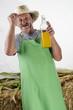 Biobauer hält eine große Flasche Orangensaft