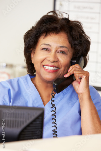 Nurse Making Phone Call At Nurses Station