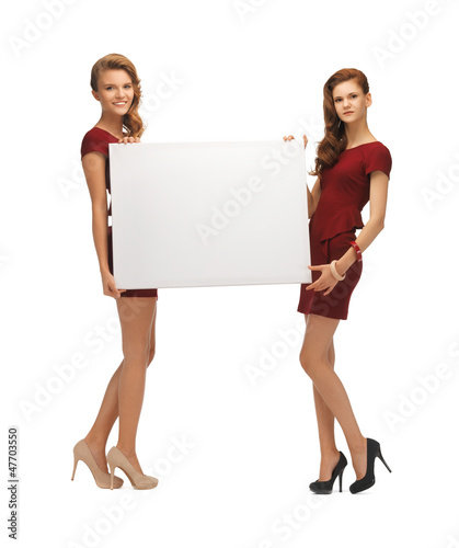 two teenage girls in red dresses with blank board