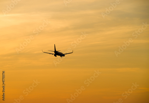 Jetliner flying against red sunset sky