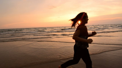 Camera moving and Asian woman running on the beach