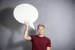 Uncertain man holding white blank speech bubble.