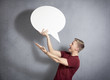 Astonished man holding empty speech bubble.
