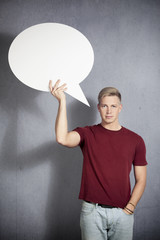 Likable man holding white blank speech bubble.