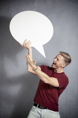 Joyful man presenting white empty speech balloon.
