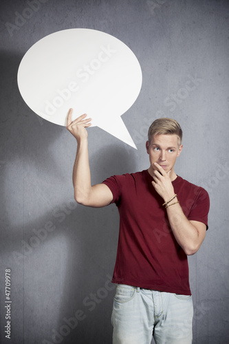 Pensive man holding white blank speech bubble.