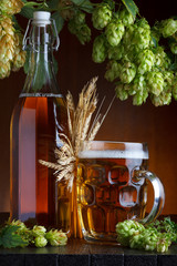 Beer bottle and glass with fresh green hop and wheat