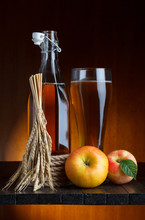 Manzana de cristal y una botella de sidra con manzanas y trigo la naturaleza muerta