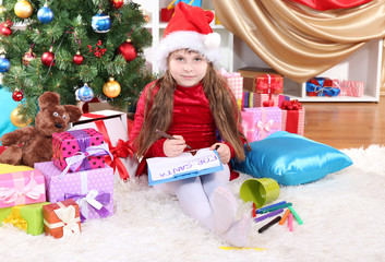 Beautiful little girl in red dress writes letter to Santa Claus