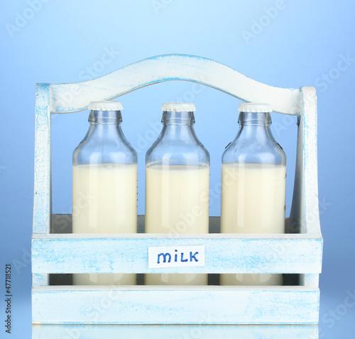 Milk in bottles in wooden box on blue background
