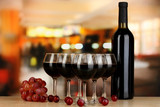 Red wine in glass and bottle on room background