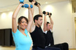 Group of three people training with gymnastic balls and dumbbell