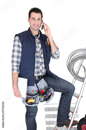 Electrician with mobile telephone stood by ladder