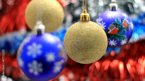 Christmas toys swinging on the background of tinsel