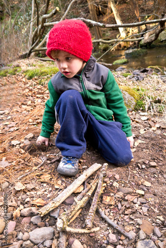 Little boy collecting fire wood on a fall day