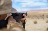 aiming rifle in the desert
