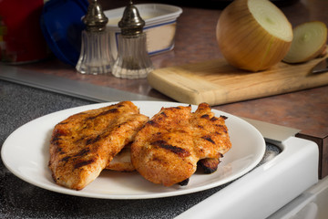 Spicy grilled chicken breast cutlets and ingredients