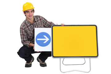 Construction worker with an arrow pointing to a blank sign