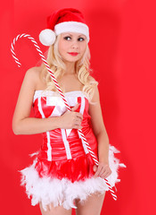 blonde Santa girl with candy cane stick on red