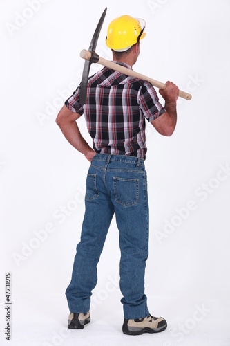 bricklayer seen from behind with pickaxe over his shoulder