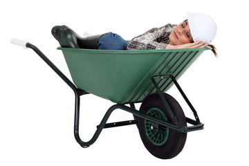 A female construction worker sleeping in a wheelbarrow.
