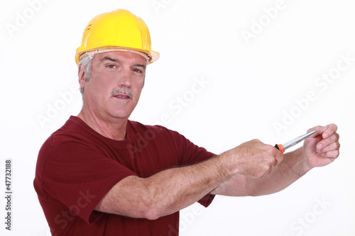 Grey haired man using screw driver