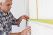 Grey haired handyman measuring wall