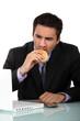 Man eating burger at desk
