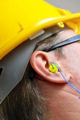 yellow earplug into the ear close up