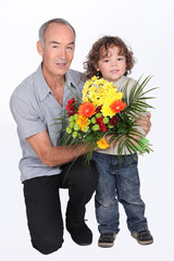a grandfather and his little son holding a flowers bouquet