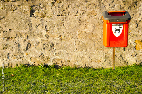 dog waste bin on stone wall in sun shine