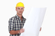 man wearing helmet and holding a blueprint