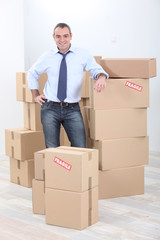Horizontal image of a man surrounded by cardboard