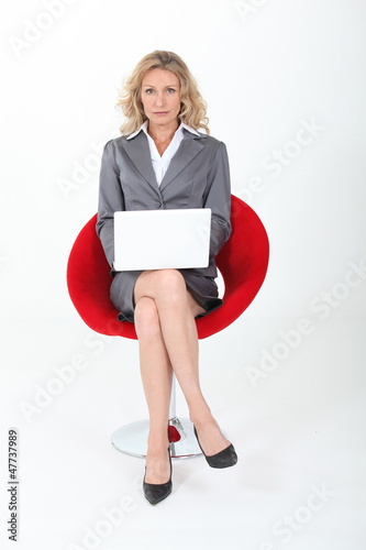 Elegant woman using laptop sitting in an armchair