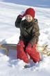 Kind auf Schlitten im Schnee wirft Schneeball
