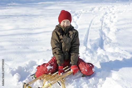 Kind beim Schlittenfahren im Winter
