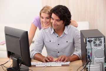 Man repairing computer for attractive blond
