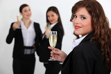 Suited women drinking champagne