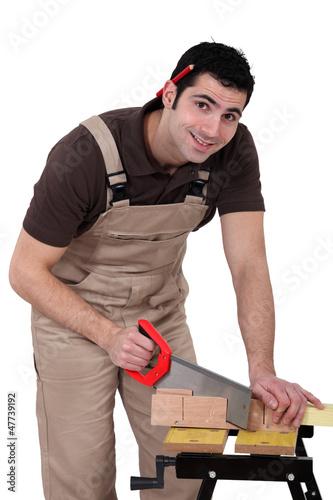 Carpenter using a handsaw
