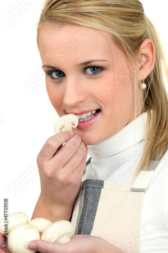 young woman smelling fresh mushrooms