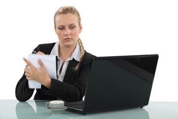 businesswoman looking at her laptop and taking notes