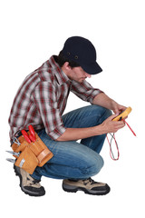 A kneeled electrician with a voltmeter.