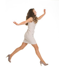 Young woman in dress jumping. Side view