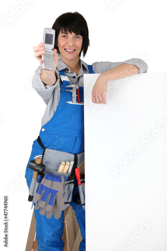 Female manual worker displaying mobile telephone