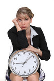 blonde with clock looking bored