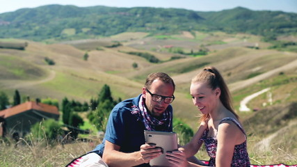 Picnic - Romantic happy couple with tablet computer in sunny nat