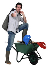 a builder posing near a wheelbarrow