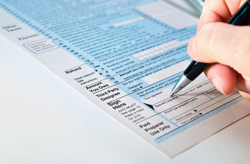Tax form 1040 with pen in hand.