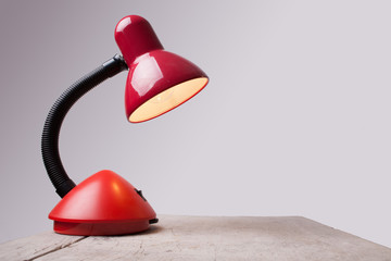isolated red lamp on wooden desk